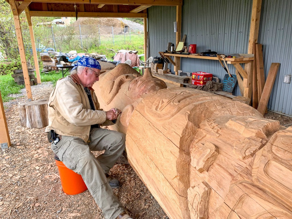 man carving totem pole in Hoonah, Alaska near Icy Strait Point