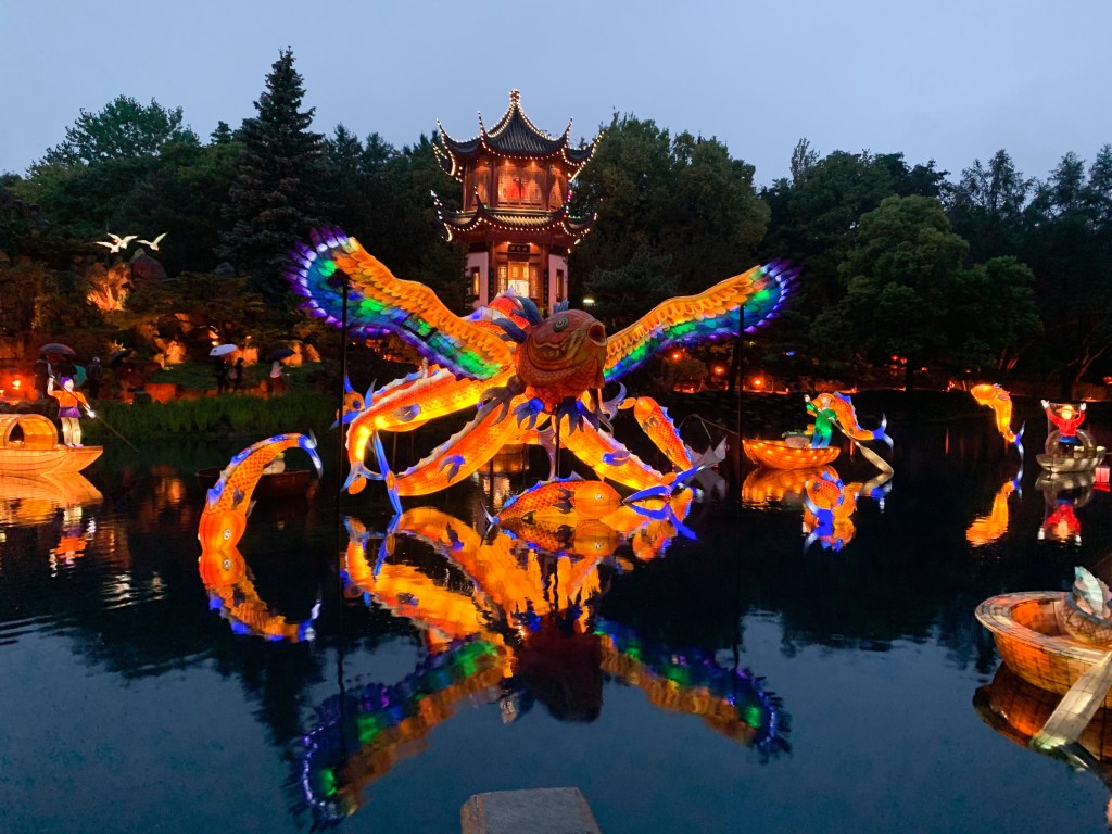Colorful mythical creature shaped Chinese lantern and other lanterns on the pond at the Gardens of Light in Montreal Botanical Garden