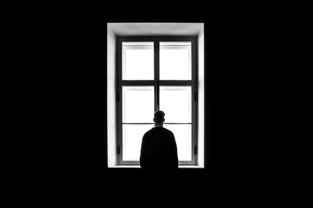 Man standing in front of window.  Business travel can be lonely.