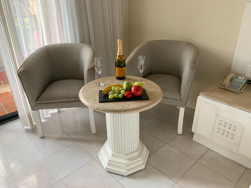 Table with champagne and fruit tray in hotel room in all-inclusive resort in Mexico.