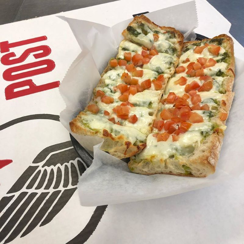 Toasted bread covered with pesto, cheese and tomatoes. The best pizza in Louisville can be found at The Post.