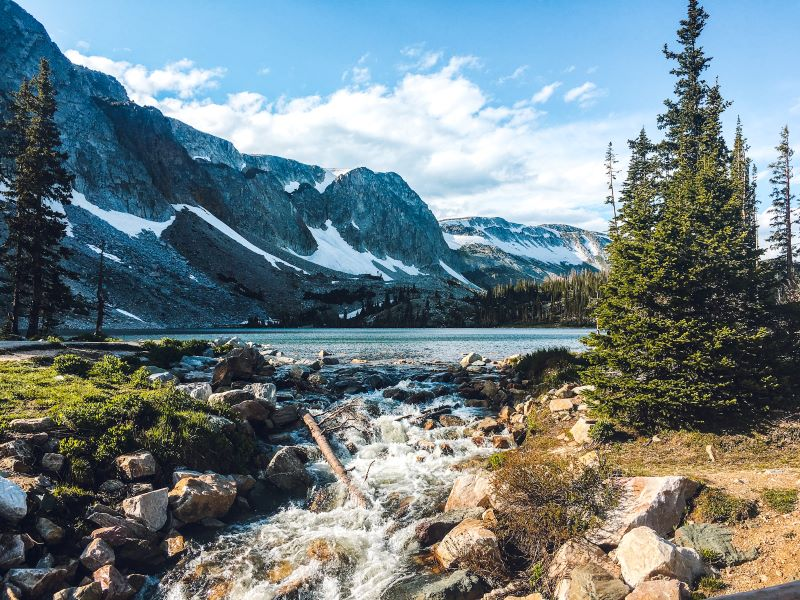 view of a lake alongside snow-capped mountains in Medicine Bow National Forest near Laramie, Wyoming