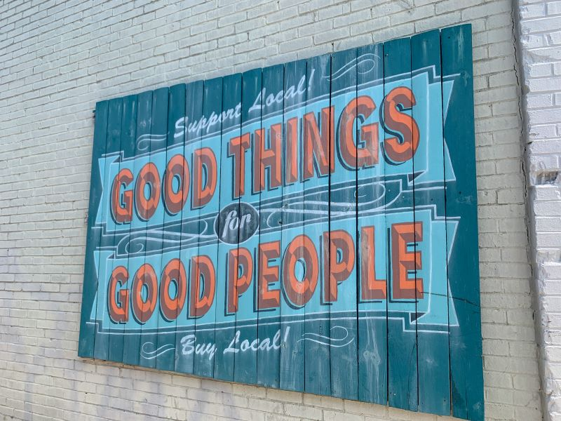 "Turquoise and orange mural that says ""support local, good things for good people, buy local."" Mural is located in the Chevy Chase shopping center in Lexington and is one of the best places to shop."