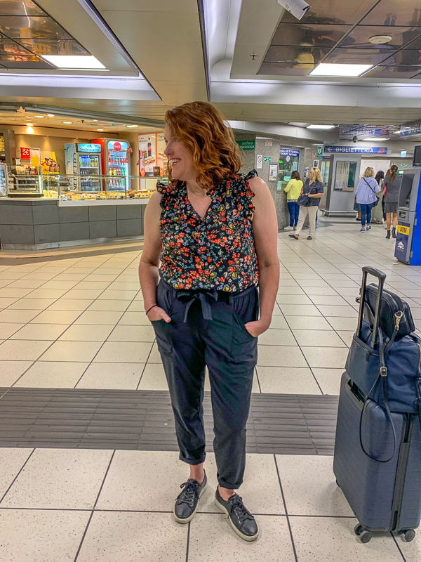 Woman standing in airport. Athelta Skyline Pants are an eco-friendly choice for gift-giving.