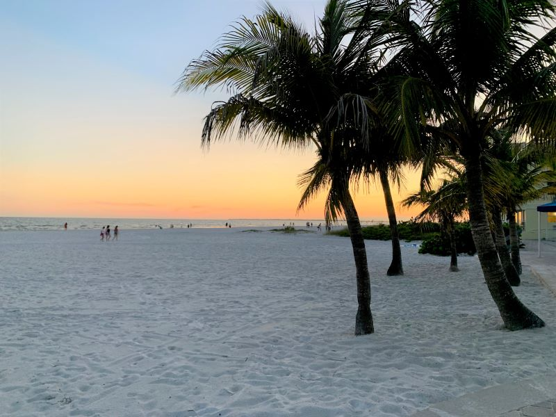sunset as people walk along white sand beach at the Neptune Fort Myers Beach