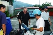 Ambassador Rafi Gamzou handing water container to locals