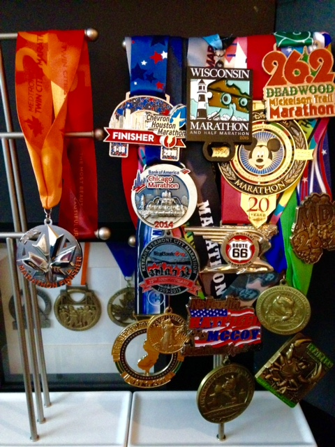 Marathon Medals as of October 7, 2015 (In box - Marine Corps, NYC, Fresno. On left stand - Twin Cities. On right stand - Houston, Chicago, Vermont, Portland, New Jersey, Wisconsin, Disney, Route 66, Hatfield McCoy, Cincinnati Flying Pig, Deadwood Mickelson, MDI, Marshall, Baltimore).