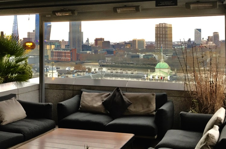 Black sofas and views out to the river Thames