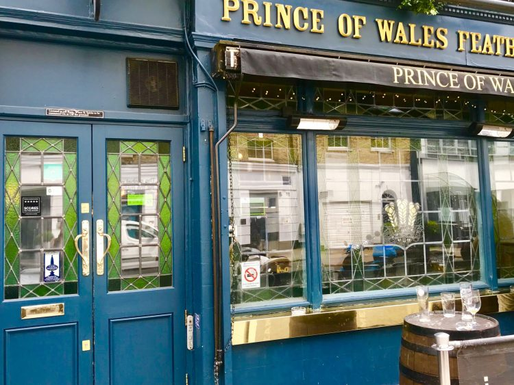 sign that says 'prince of whales feathers'  front of the pub
