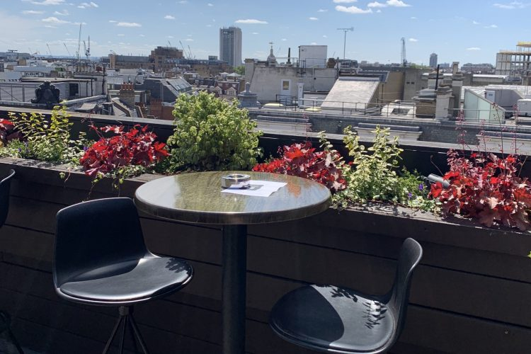 2 chairs and a table on rooftop bar at Aqua Oxford street