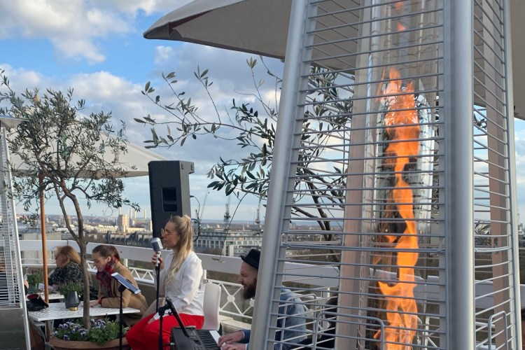 a singer with a microphone and a fire and heater on a rooftop bar
