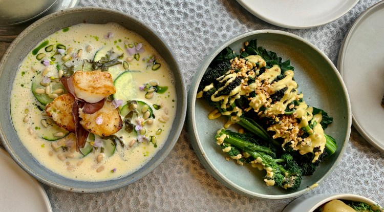 A round bowl with scallops and a bowl with broccoli with a yellow sause over both