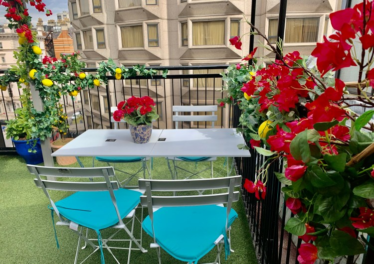 empty table and chairs surrounded by red flower and lemons