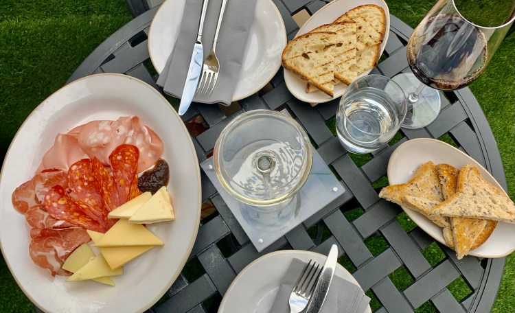 Glass of red wine, bread on a plate and selection of meats and cheeses on a plate