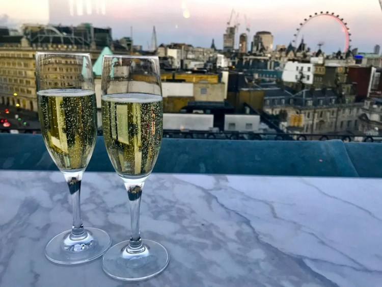 2 champagne glasses on a rooftop bar with the london eye in the background