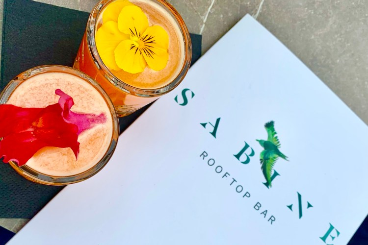 2 pretty drinks with flowers on them and a menu