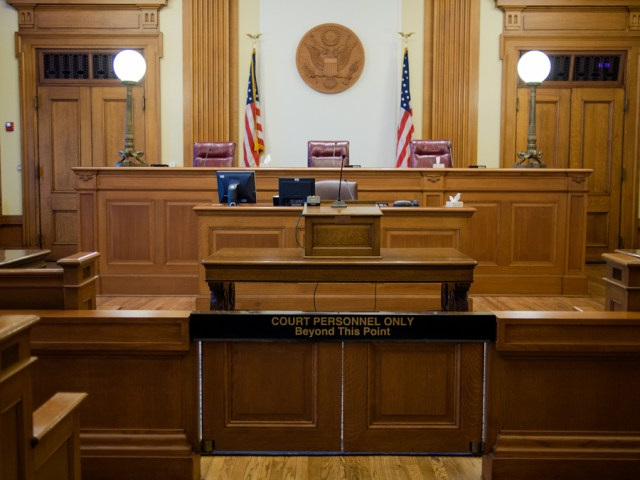An empty courtroom with oak furnishings. There are seats for three judges.