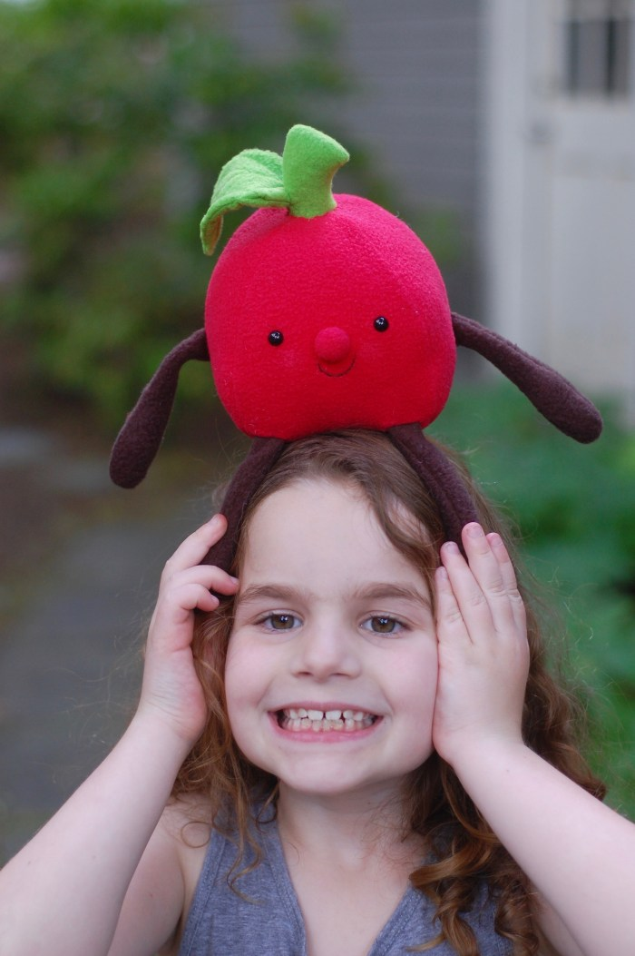 plush apple on little girls head