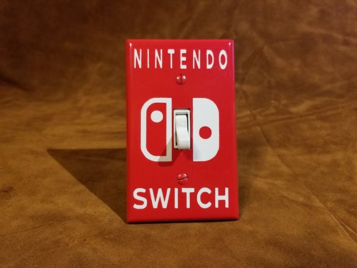"A red light switch plate that says ""Nintendo Switch"""