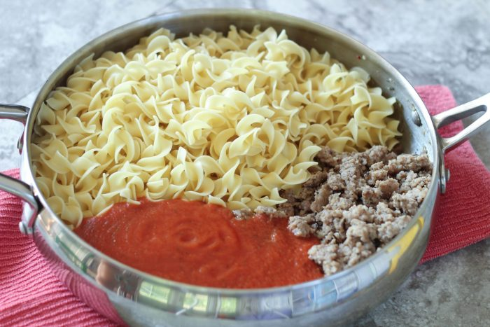 Noodles with Sausage and Creamy Marinara - This easy dinner recipe is a crowd pleaser for kids and adults alike. It's quick, cheap, and absolutely delicious! The creamy sauce pairs well with the sausage and fluffy noodles. Yum!