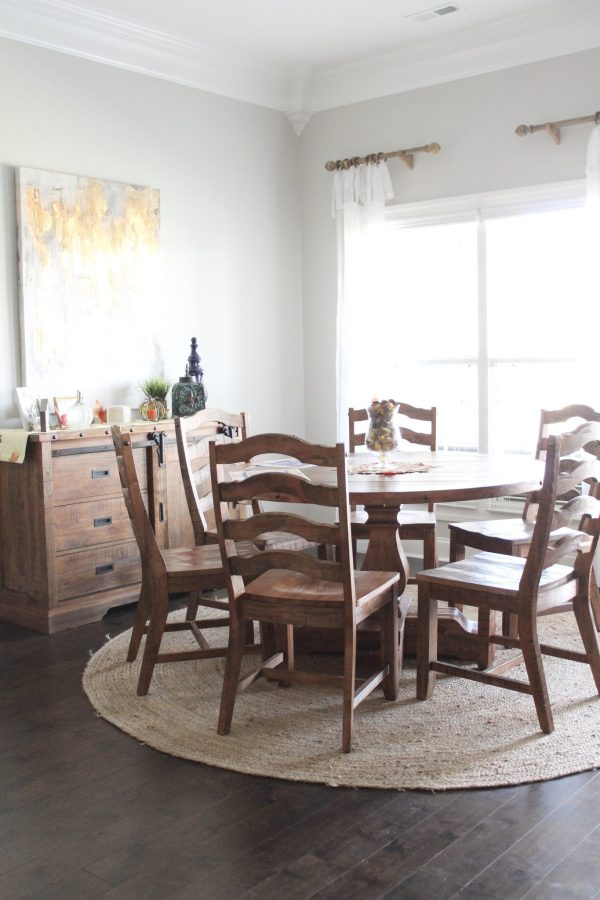 """We love this family kitchen eating area! In this post, I share details about our new 54"""" round kitchen table, our 8' round jute rug, matching sideboard, curtains, rods, and more. Gather new ideas and inspiration for big or small kitchens. This specific round table area is near a window with a big wall for decorating. Click here to read more and get links to resources."""