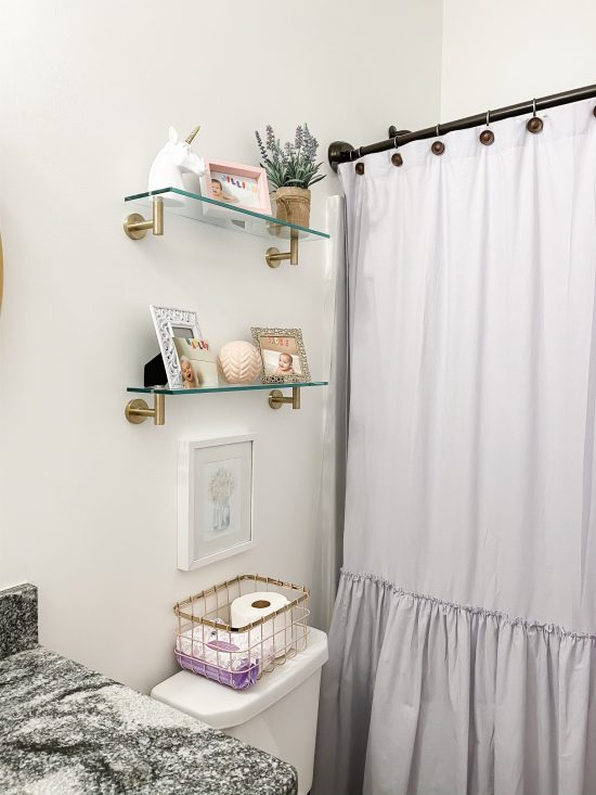 Hall Bathroom Makeover for little girls: This hallway full bathroom follows a white, gold, and pastel color scheme and was completed for less than $600. All sources included for the mirror, light fixture, shelves, shower curtain, shower curtain liner, bath mat, towels, bath hooks, and more. Enjoy!