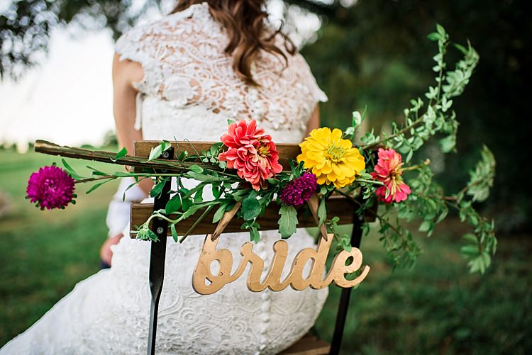 Bride Lace Bridal Gown With Buttons Wooden Chair Multicoloured Floral Decoration Gold Metallic Bride Sign Ethereal Boho Wedding Ideas http://perfectcapturephoto.com/