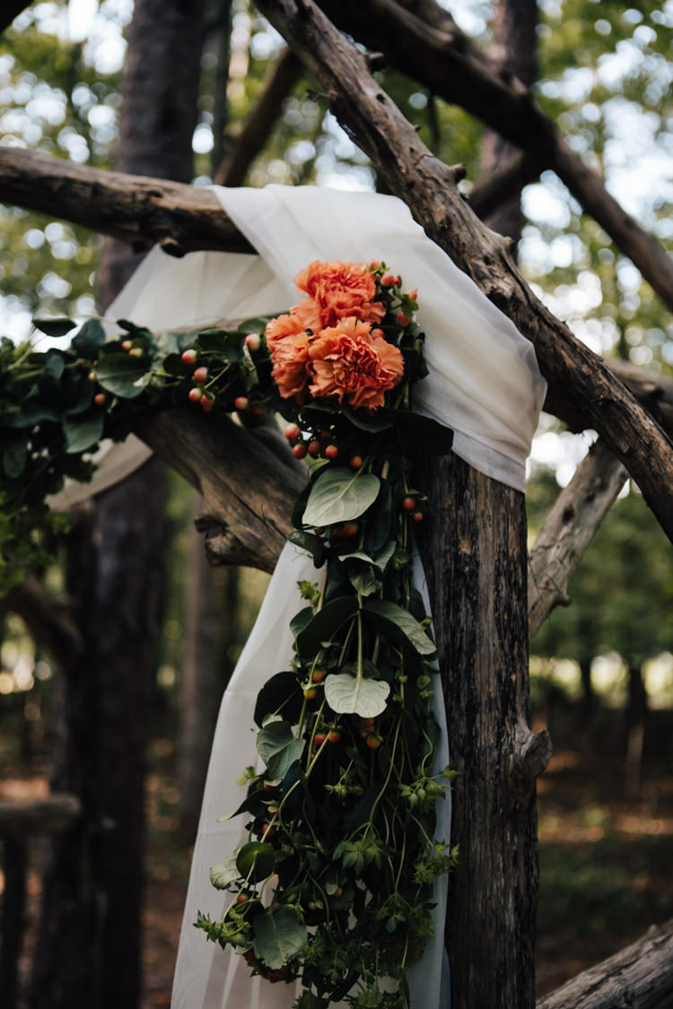 Outdoor Ceremony Decorated Wooden Arbour White Organza Orange Florals Greenery Adventure Inspired Woodland Wedding North Carolina http://www.amandasuttonphotography.com/