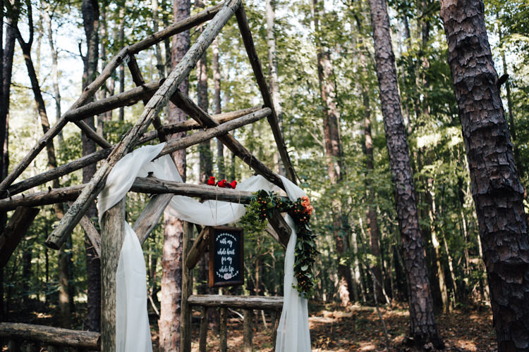 Outdoor Ceremony Decorated Wooden Arbour White Organza Orange Florals Greenery Red Birds DIY Quote Sign Blackboard Adventure Inspired Woodland Wedding North Carolina http://www.amandasuttonphotography.com/