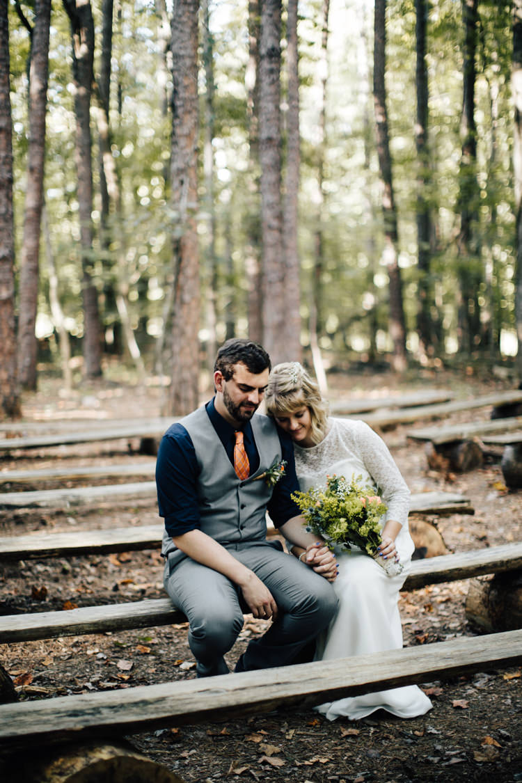 Outdoor Ceremony Location Bride Handmade Lace Bridal Gown Bouquet Groom Grey Vest Pants Navy Blue Shirt Orange Checkered Tie Wooden Bench Seating Adventure Inspired Woodland Wedding North Carolina http://www.amandasuttonphotography.com/
