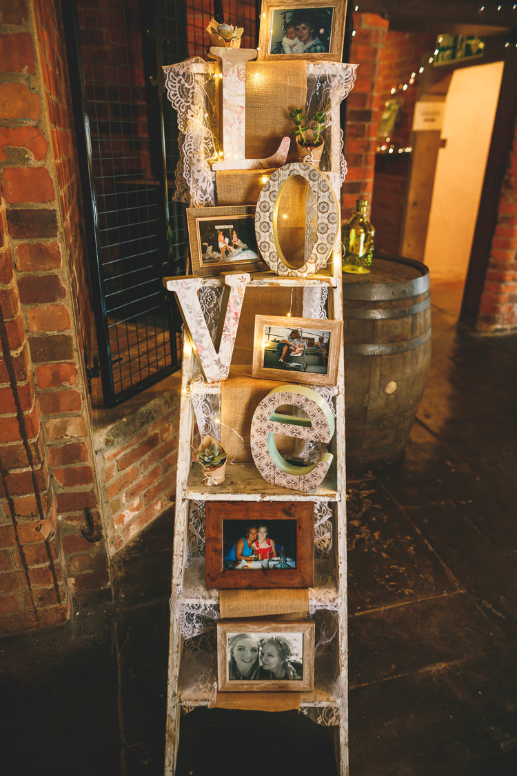 Stepladder Display LOVE Lace Photographs Memories Fairy Lights Rustic Barn Red Gold Glam Wedding https://garethnewsteadphotography.com/