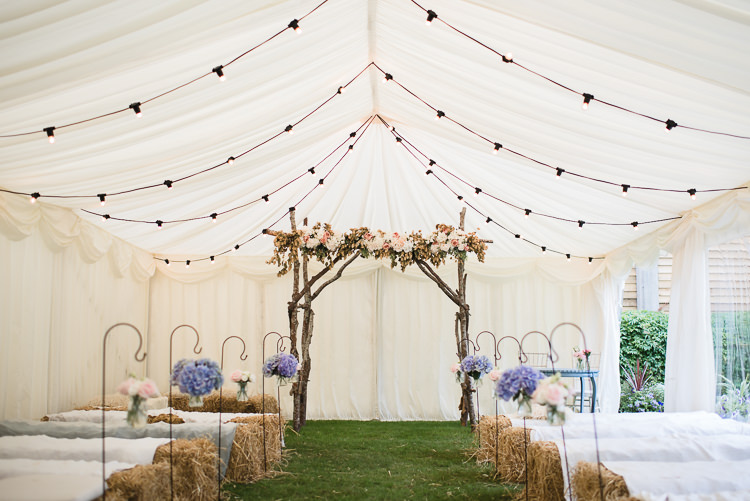 Marquee Ceremony Backdrop Arbour Flowers Floral Pastel Shepherds Crook Paper Pom Pom Festoon Lighting Personal Homegrown Country Farm Wedding https://www.emmahare.com/