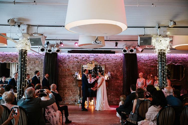 Urban Decor Ceremony Aisle Hanging Floral Curtain Bride Groom Cape Dress | Glitter Dinosaurs City Wedding https://struvephotography.co.uk/
