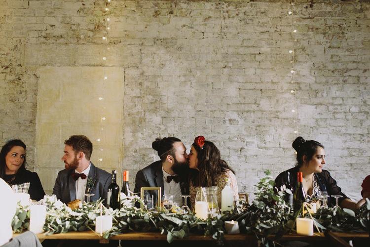 Bride Bridal Dress Gown Lace Long Sleeve Sweetheart Red Burgundy Rose Flower Crown Grey Tweed Groom Bow Tie Top Table Greenery Garland Candles Alternative London Warehouse Wedding https://www.lukehayden.co.uk/