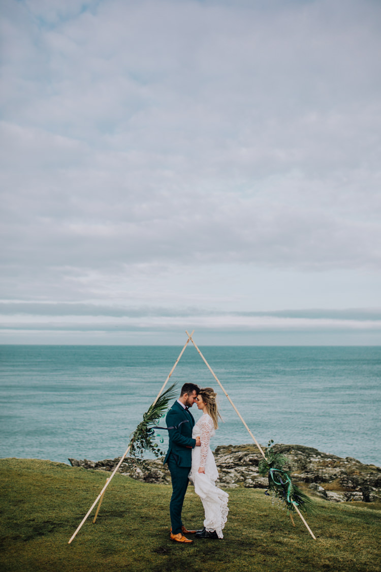 Triangle Wooden Backdrop Flowers Greenery Ceremony Ocean Clifftop Elopement Wedding Ideas North Wales https://www.claracooperphotography.com/