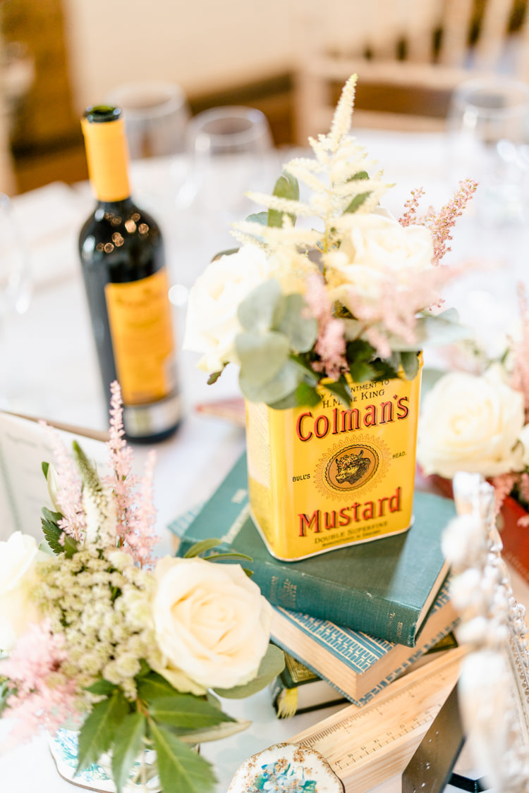 Table Centre Vintage Books Mustard Tin Flowers Rose Eucalyptus Nostalgic Honest British Loseley Park Wedding Surrey https://www.johnbarwoodphotography.co.uk/