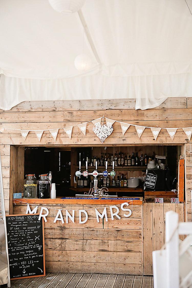 Wooden Shed Bar Bunting Mr & Mrs Chalkboard Menu Pretty Sparkly Lusty Glaze Beach Cornwall Wedding http://victoriamitchellphotography.com/
