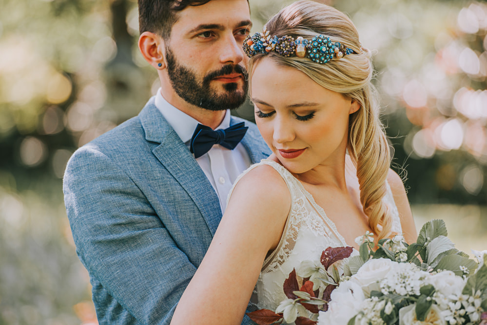 Secret Dresshouse Ethereal Bride Bridal Gown Storm Hurricane Candles Lanterns Leaf Foliage Flower Florals Bouquet Jewelled Crown Blue Linen Jacket Bow Tie Groom River Romance Wedding Ideas Mindy Coe Photography