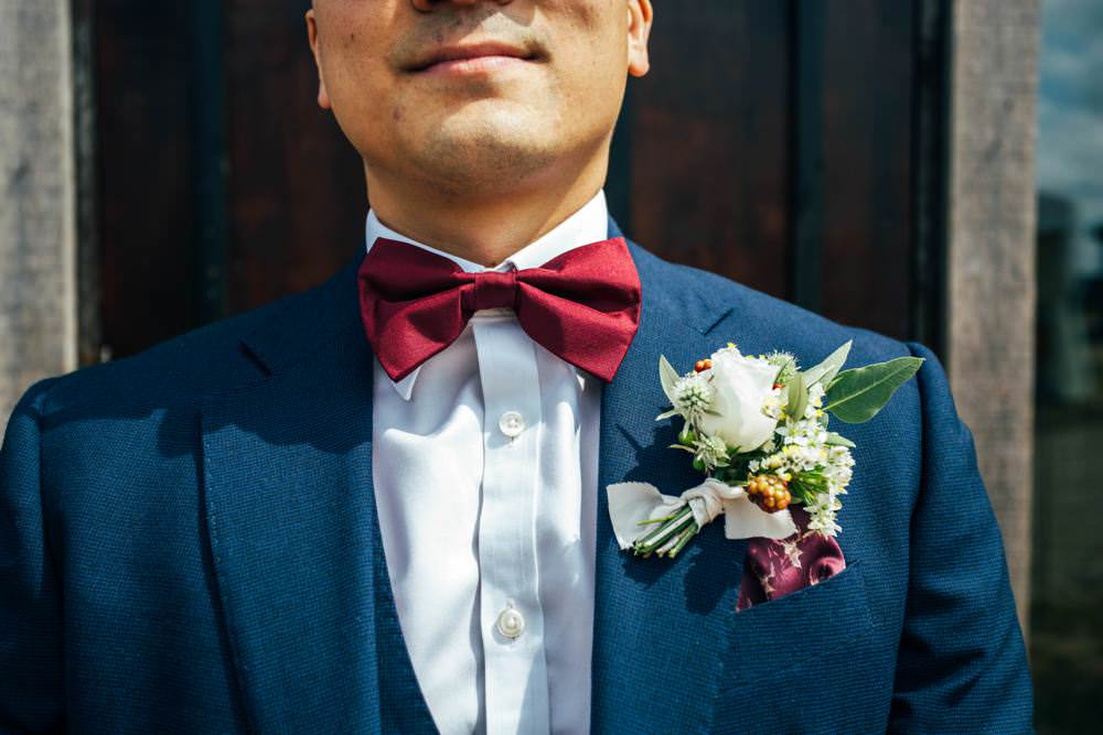 Groom Groomsmen Blue Suits Burgundy Bow Ties Buttonhole Flowers Berry Rose Thistle Long Barn Wedding Three Flowers Photography