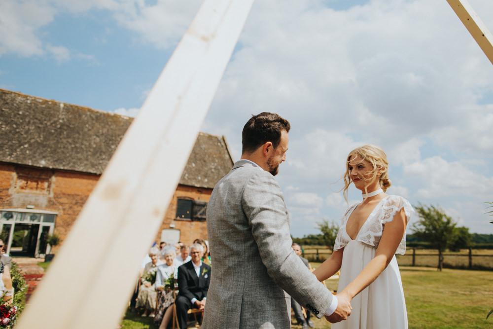 Aisle Ceremony Outdoor Persian Rug Wooden Triangle Backdrop Palm Plants Godwick Great Barn Wedding Joshua Patrick Photography