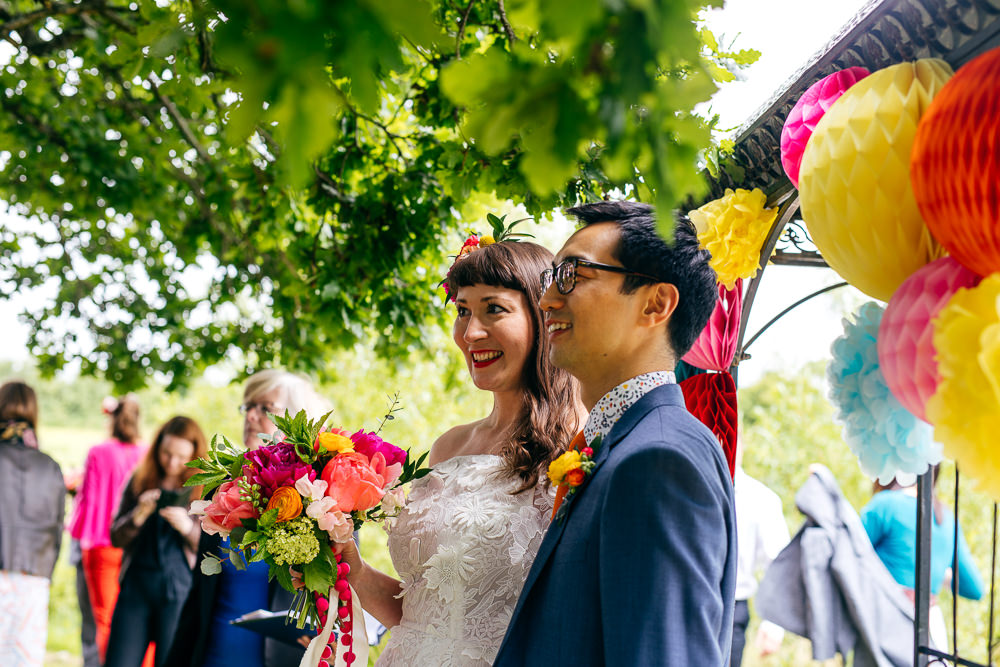 Outdoor Ceremony Arch Lanterns Pom Poms Rainbow Colourful Decor Backdrop Ash Barton Estate Wedding Jordanna Marston Photography