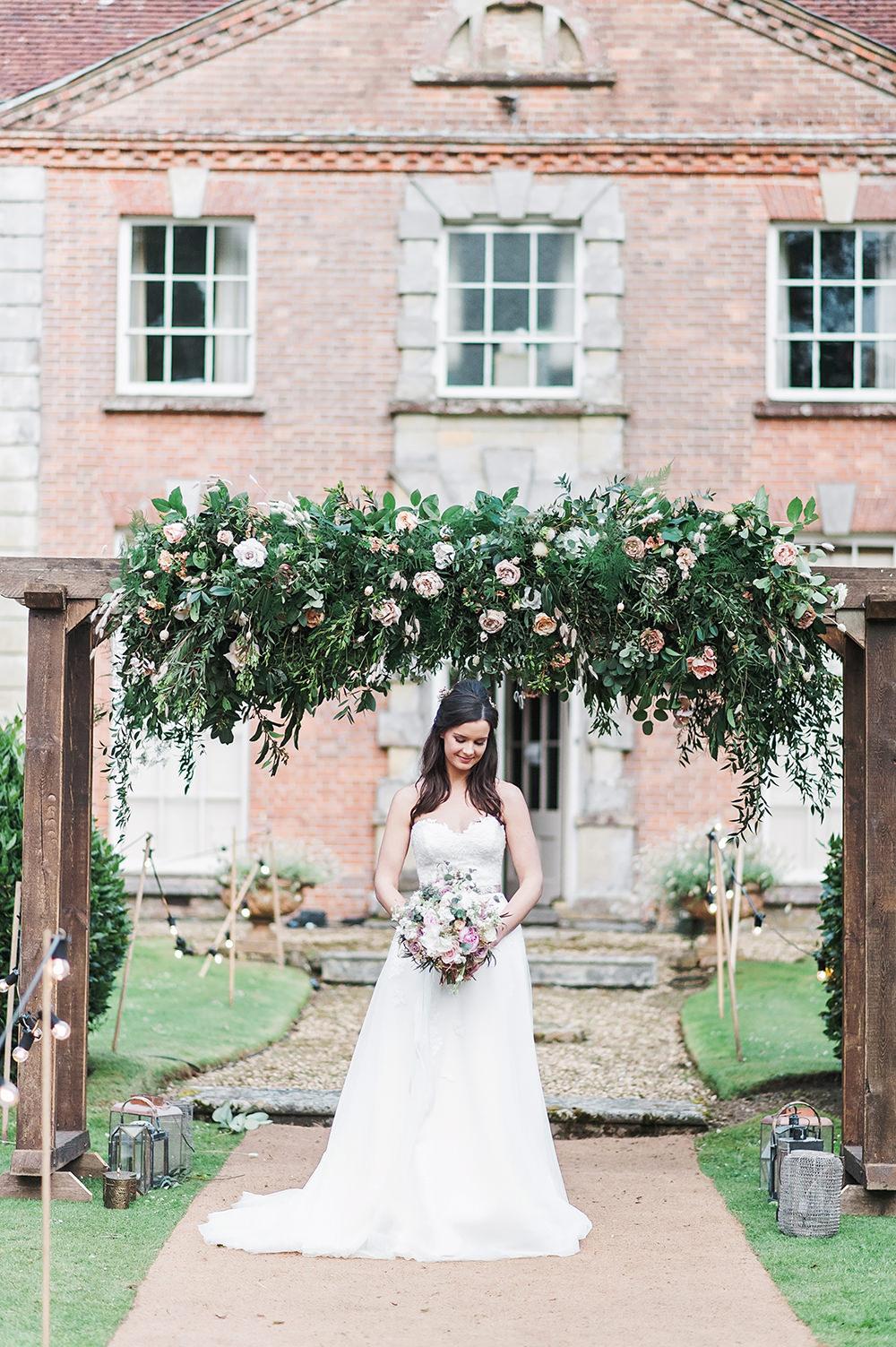 Bride Bridal Gown Dress Strapless Sweetheart Neckline Ribbon Belt Pink Greenery Foliage Rose Arch Edmondsham House Wedding Darima Frampton Photography