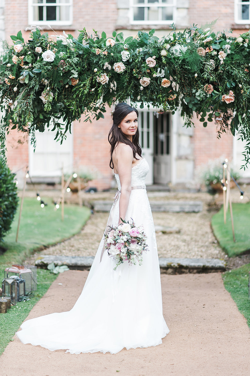 Bride Bridal Gown Dress Strapless Sweetheart Neckline Ribbon Belt Pink Foliage Greenery Rose Arch Archway Edmondsham House Wedding Darima Frampton Photography