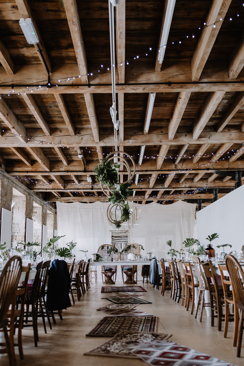 Bohemian Reception Room Decor Macramé Persian Rugs Hanging Hoops Greenery Foliage Peacock Chairs Botanical Industrial Wedding Caitlin and Jones Photography