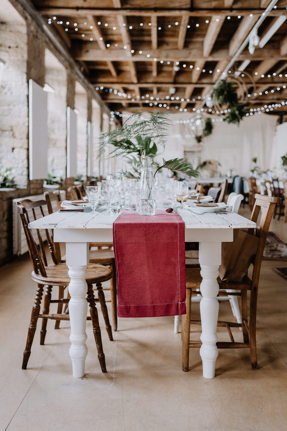 Bohemian Reception Room Decor Persian Rugs Hanging Hoops Greenery Foliage Wooden Chairs Botanical Industrial Wedding Caitlin and Jones Photography
