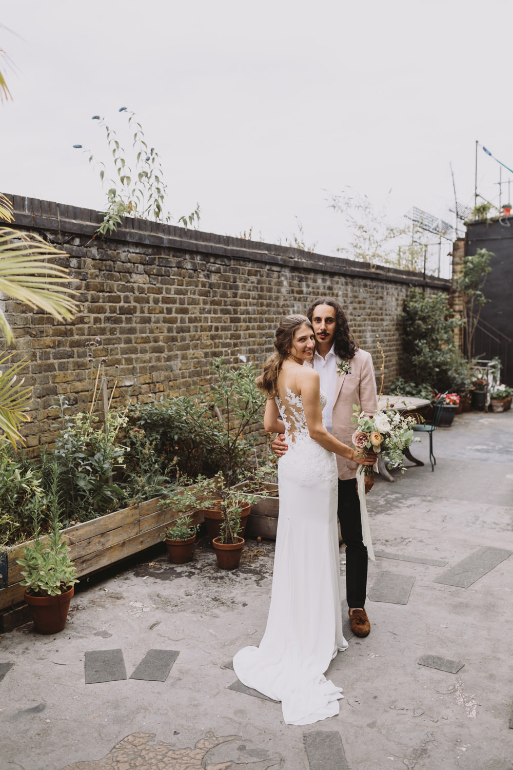Bride Bridal Sleeveless V Neck Fit and Flare Train Pronovias Dress Gown Pink Jacket Reiss Groom Wild Bouquet Loose Handtied Rose Illusion Back Lace Tram House Wedding Luke Hayden Photography