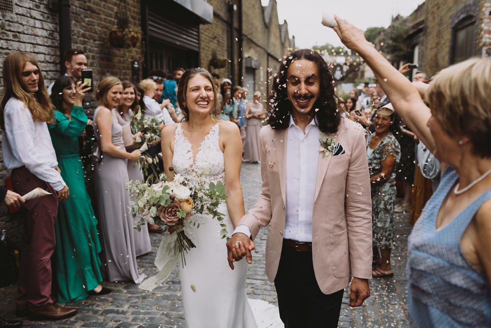 Bride Bridal Sleeveless V Neck Fit and Flare Train Pronovias Dress Gown Pink Jacket Reiss Groom Wild Bouquet Loose Handtied Rose Confetti Tram House Wedding Luke Hayden Photography