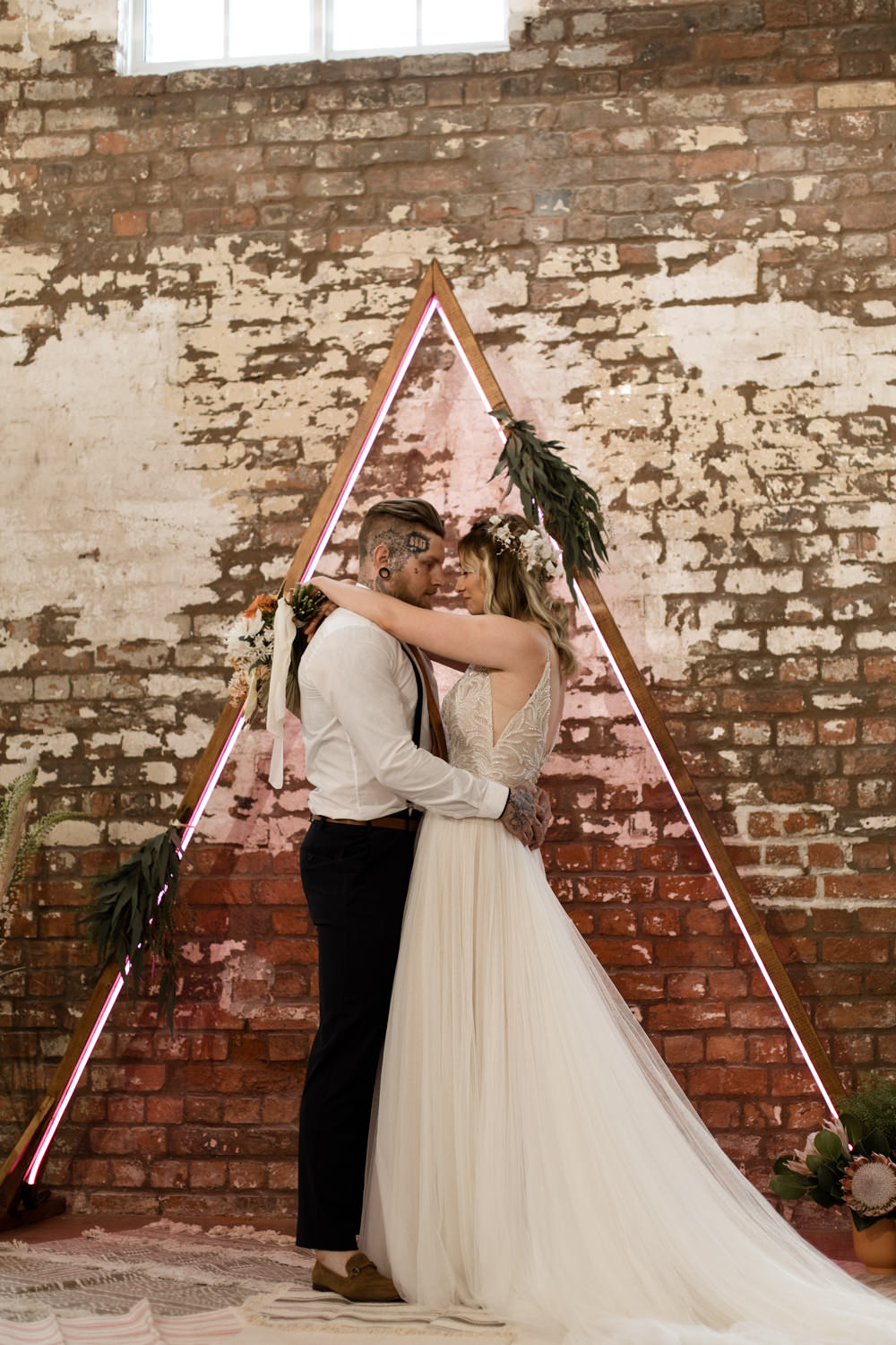 Triangle Backdrop Wooden Frame Neon Lighting Ceremony Greenery Foliage Moroccan Wedding Ideas Emma Louise Photography