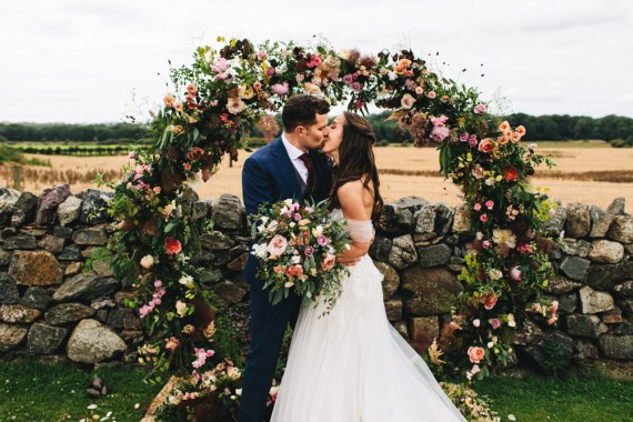 Outbuildings Wedding Jessica O'Shaughnessy Photography Moon Gate Flower Arch Ceremony Aisle Flowers Greenery Foliage Sweetpeas Freesias Peony Rose Burgundy Pink