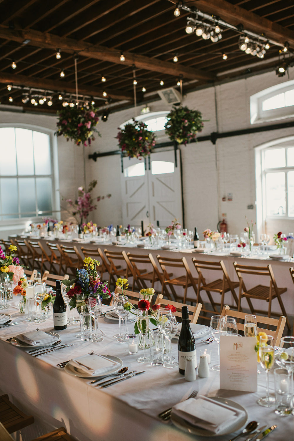 Ceiling Hanging Suspended Flowers Decor Spring Coral Peony Natural Wild Colourful Long Tables Riverside London Wedding Ellie Gillard Photography